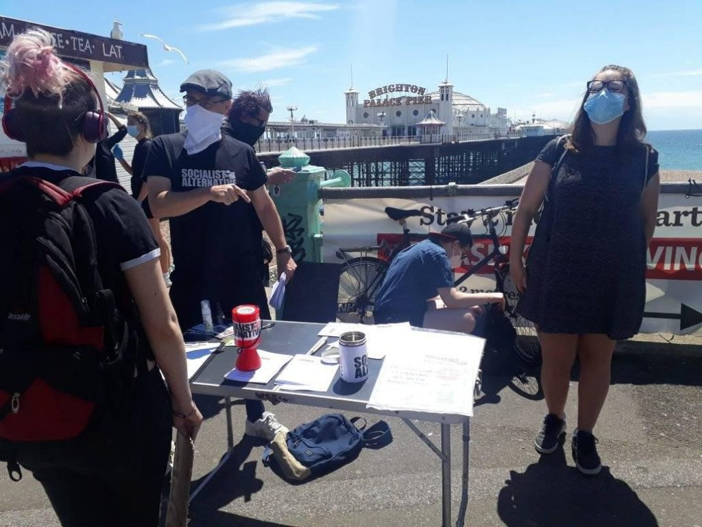 People with rattling tins by a table with the Brighton pier in background