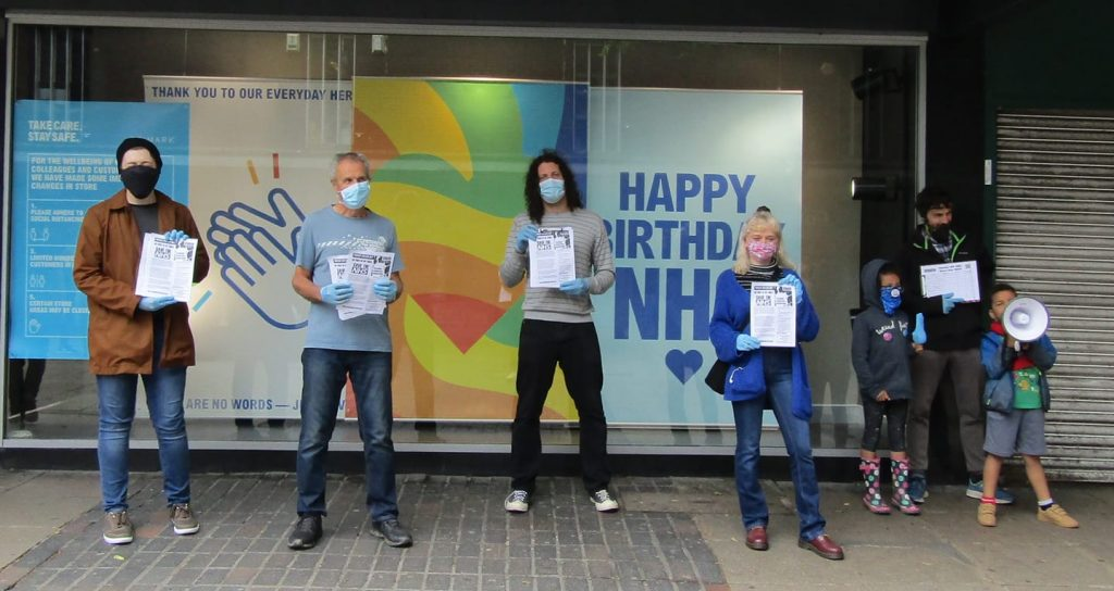 People holding signs in front of sigh saying 'Happy birthday NHS'