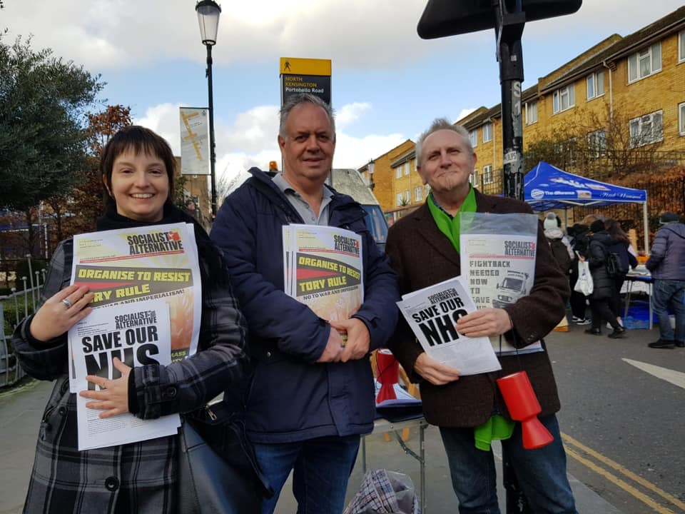 People holding the Socialist Alternative newspaper with the headline 'organise to resist Tory rule'